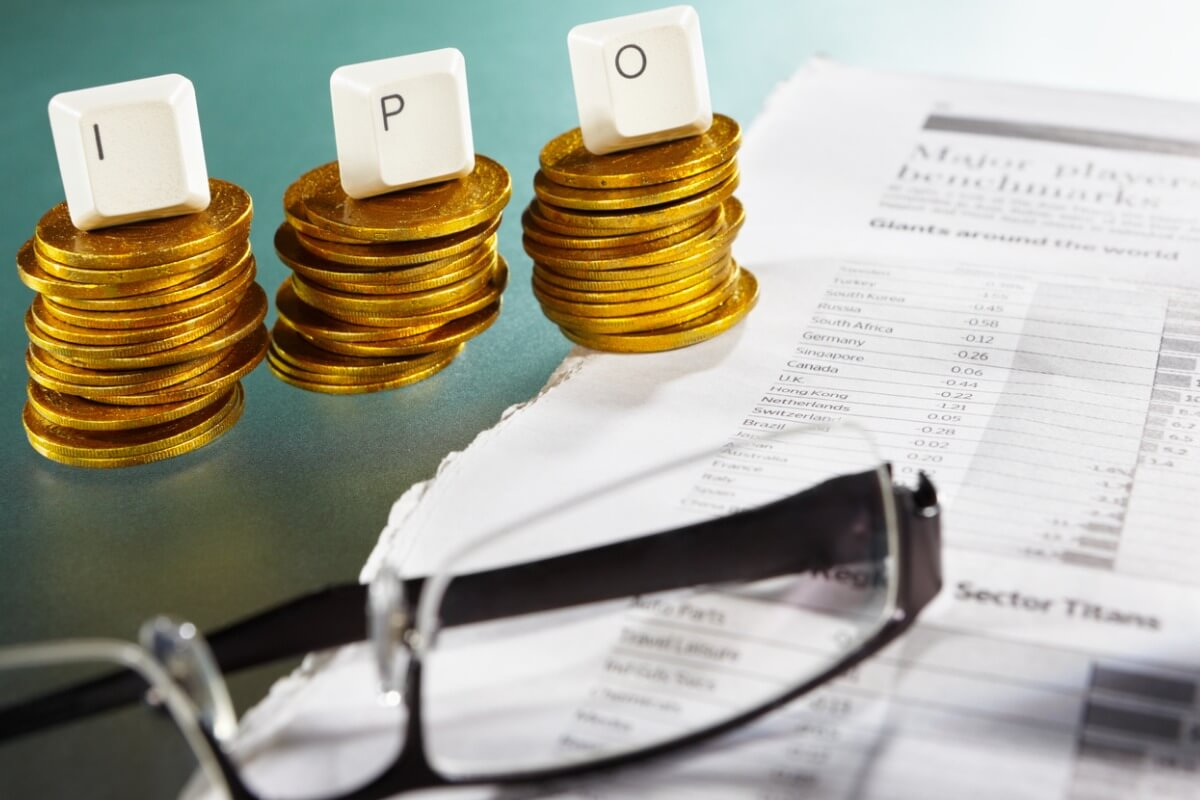 IPO letter on each block over gold coins stacks with newspaper and glasses