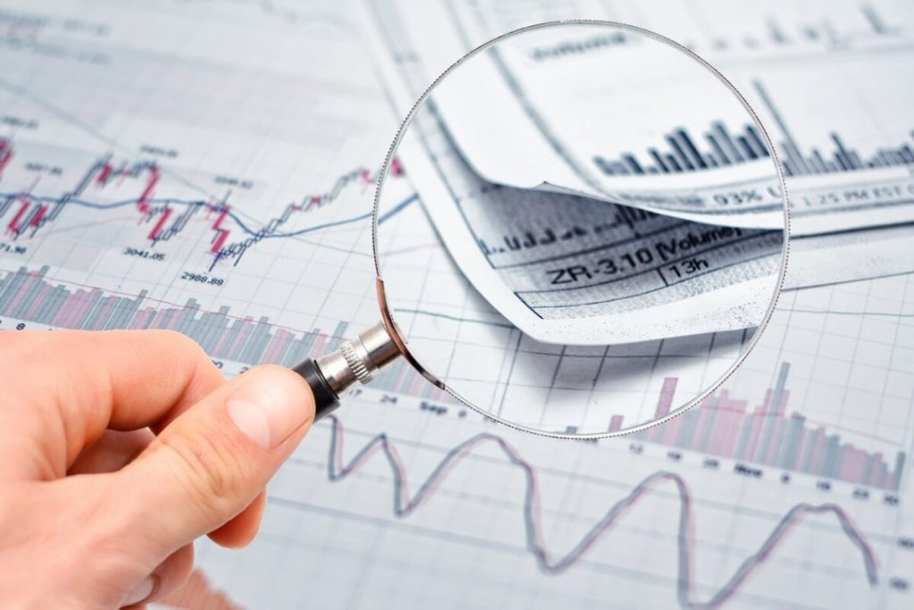 A magnifying glass over a stock chart finding growth stocks, a secondary stock offering or small-cap growth stocks