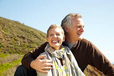 Senior couple sitting on a grassy hill while smiling