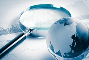 magnifying glass and globe over stock graph document